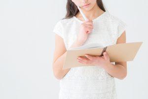 ノートを見て考える女の子