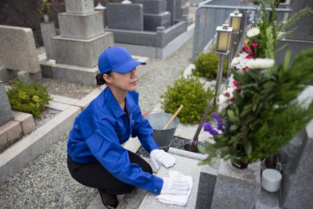 墓掃除をする女性